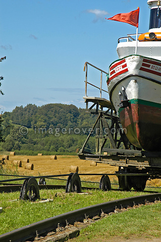 Tourist boat on cable-cradle approaching uphill basin: Overland transportation of boats on rail cars at the Elblag Canal (Polish: Kanal Elblaskie, German: Oberlaendischer Kanal), Masuria, Poland, Europe. No releases available. ---Info: A system of rail-mounted cable trolleys on skipways and traditional locks are connecting the various sections of the Elblag Canal. A 100 metre difference in water levels is overcome during a length of 80 km between Ostroda and Elblag. The rail lift devices are mechanically driven by water power.--- HISTORY: The canal was designed in 1825-1844 by Georg Steenke, carrying out the commission given by the king of Prussia. Construction began in 1844. As the route was not important enough to justify building expensive, traditional locks between lakes, an ingenious system of tracks was employed instead, though the canal includes a few locks as well. Built originally under the name Oberländischer Kanal (Overland Canal) and situated in the Kingdom of Prussia, it was opened in 1860. Since 1945 the canal has been located in Poland. After wartime damage was repaired, it was restored to operation in 1948. Today it is used mainly for recreational purposes. It is considered one of the most significant monuments related to the history of technology on the territory of modern Poland..