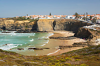Portugal, Alentejo, Zambujeira do Mar: kleiner Urlaubsort am Atlantik im Parque Natural do Sudoeste Alentejano e Costa Vicentina | Whitewashed town on cliffs above beach and breaking waves of the Atlantic sea in noon sun, Zambujeira do Mar, Alentejo region, Portugal, Europe