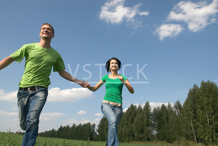 Young couple running trough field