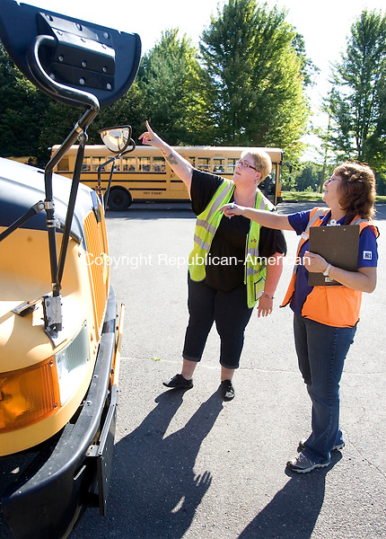 MIDDLEBURY CT. 25 August 2014-082514SV07-From left, Tricia Sandulli checks a bus with Lise Baummer, safety coordinator, at First Student bus company in Middlebury Monday. The drivers were getting ready for the first day of school Tuesday.<br /> Steven Valenti Republican-American