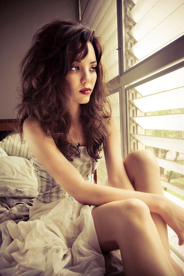 Model bathed in window light wearing tulle.