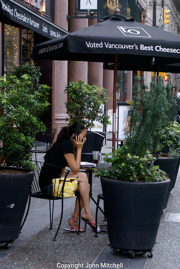 Young Asian woman speaking on a cell phone in an outdoor cafe, Vancouver, British Columbia, Canada