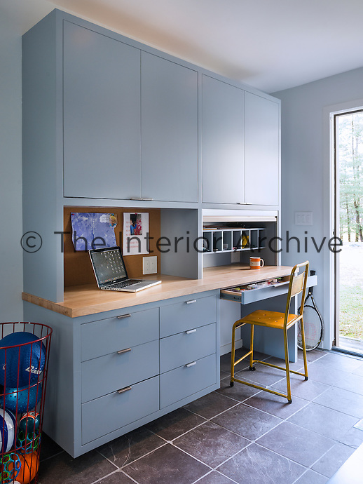 A neat home office with a grey blue built-in desk, cupboard and drawer unit.