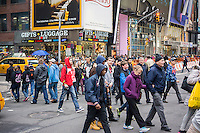 Throngs of tourists cross Seventh Avenue in Times Square in New York on Friday, April 10, 2015. A strong dollar is making it less attractive to visit New York (and spend money!) possibly cutting into the tourism business. The tourism industry generates $60 billion dollars going into the New York economy. 55 million people visited the city last year with tourism jobs jumping 22% in the last decade.  (© Richard B. Levine)