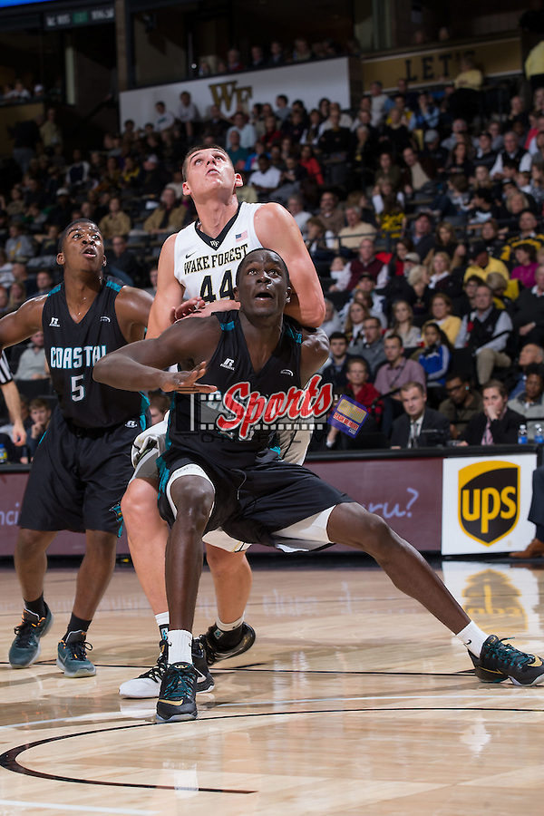 Badou Diagne (23) of the Coastal Carolina Chanticleers boxes out Dinos Mitoglou (44) of the Wake Forest Demon Deacons during second half action at the LJVM Coliseum on December 18, 2015 in Winston-Salem, North Carolina.  The Demon Deacons defeated the Chanticleers 83-77.  (Brian Westerholt/Sports On Film)