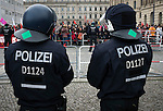Police officers in riot gear watching counter-protestors before a demonstration by the Alternative für Deutschland (AfD) political party in Berlin. Around 5000 supporters of the AfD took part in the march and rally through central Berlin calling on German Chancellor Angela Merkel to halt the influx of refugees into the country. Around one million refugees from the Middle East and north Africa arrived in Germany during 2015, 50,000 of whom came to Berlin.