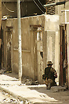 A British soldier kneels in the shade as he covers the entrance to an alleyway during a liaison visit to an Iraqi government department in Basrah City.