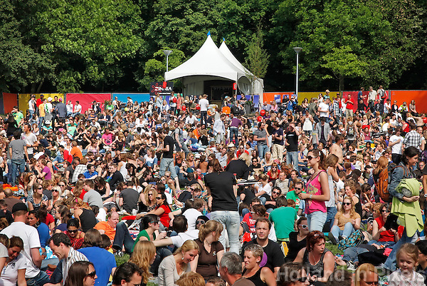 Bezoekers van een festival zitten op het gras