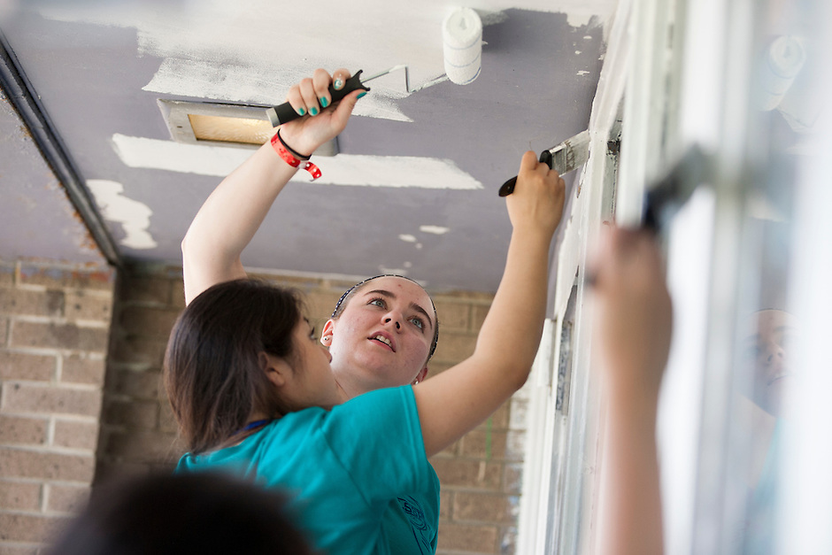 "Members including Megan Laufenberg, center, paint an entryway during ""Circle the City with Service,"" the Kiwanis Circle K International's 2015 Large Scale Service Project, on Wednesday, June 24, 2015, at the Friendship Westside Center for Excellence in Indianapolis. (Photo by James Brosher)"