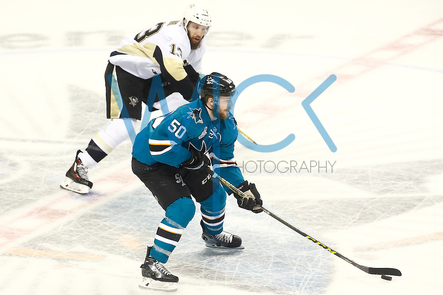 Chris Tierney #50 of the San Jose Sharks carries the puck past Nick Bonino #13 of the Pittsburgh Penguins in the first period during game four of the Stanley Cup Final at the SAP Center in San Jose, California on June 6, 2016. (Photo by Jared Wickerham / DKPS)