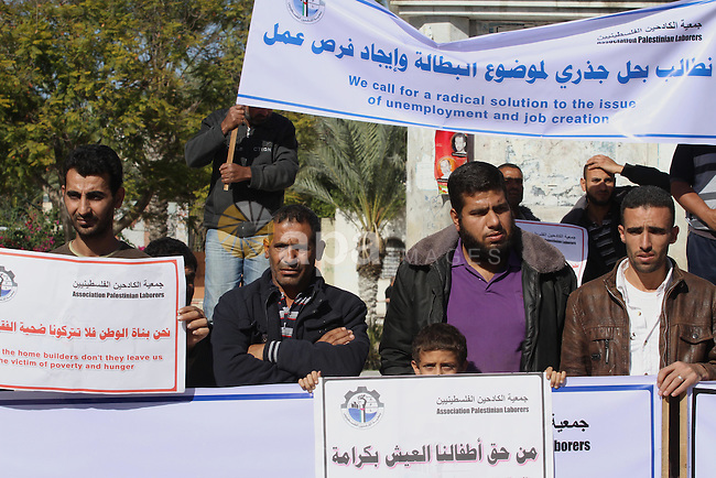 Palestinians hold banners during a protest to demand their rights and the end of the blockade on Gaza strip, in Gaza City, Nov. 09, 2014. Photo by Mohammed Asad