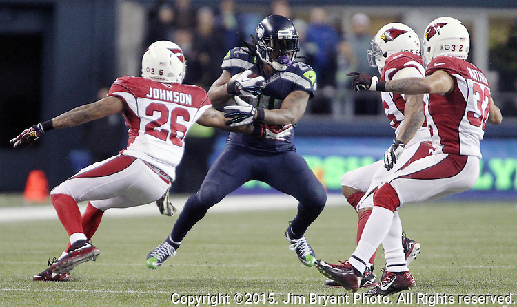 Seattle Seahawks running back Marshawn Lynch rushes past  Arizona Cardinals  Deone Johnson (20),  LaMarr Woodley (56) and Tyrann Mathieu (32) at CenturyLink Field in Seattle, Washington on November 15, 2015. The Cardinals beat the Seahawks 39-32.   ©2015. Jim Bryant photo. All Rights Reserved.