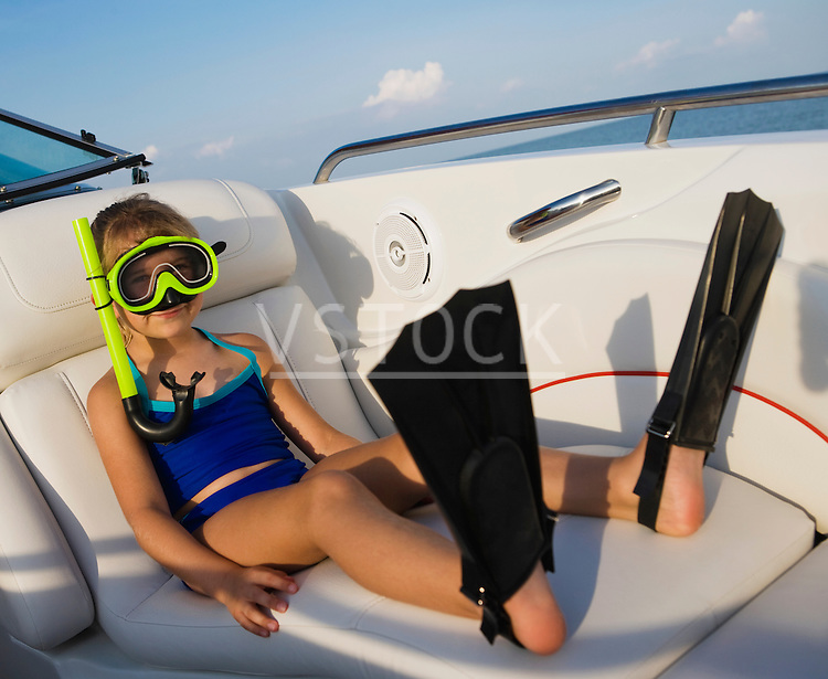 Young girl (6-8) wearing snorkeling gear in boat