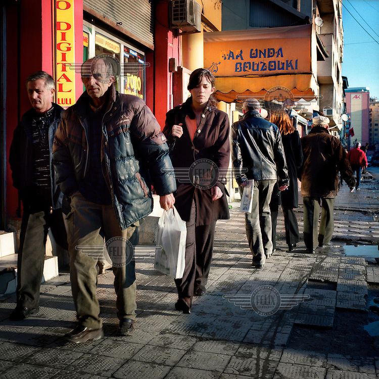 People walk through the streets of Tirana.