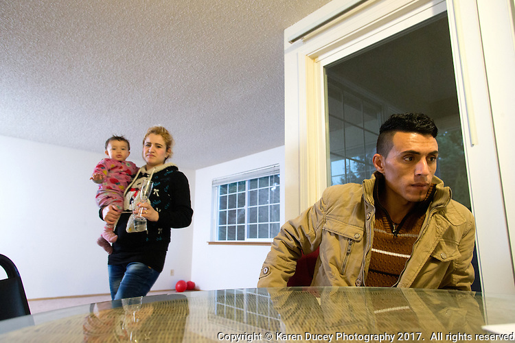 Shatha Sulaiman Kheder, 27, (left) her son Steven Adil Kheder, 10 months, and her husband Adil Kheder Nimr, 27, (right) at home in their new apartment in Tukwila, Wash. on January 30, 2017. The family arrived in the United States as refugees from Iraq on January 19, 2017, the day after Donald Trump was sworn in as the 45th president of the United States. They are concerned about thirteen of their family members still in Iraq. Trump signed an executive order last Friday restricting immigration from seven Muslim countries, suspending all refugee admission for 120 days, and bans all Syrian refugees indefinitely.  (Photo by Karen Ducey)