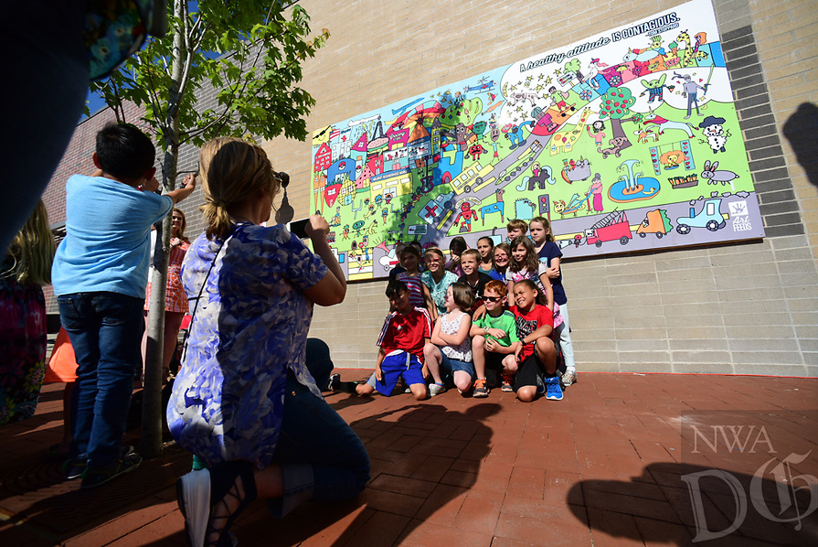 Northwest Arkansas Democrat Gazette/SPENCER Ginger Stegall a 2nd grade teacher at R.E. Baker takes a picture of her students infront of the mural students at the elementary school unveiled Tuesday May 16, 2017,  on the side of the Walmart Neighborhood Market in downtown Bentonville. Arts Feeds with help of sponsorships by the Sharon and Terry Berkstresser Fund, Walmart Marketing Department and the Walmart Museum worked with the school to create the mural. It is the first mural Art Feeds has done in Bentonville and the 30 Mural the group has done in Northwest Arkansas.