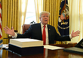 United States President Donald J. Trump makes remarks to the press during an event to sign the $1.5 trillion tax cut bill, stacked on his desk, in the Oval Office of the White House, December 22, 2017, in Washington, DC, prior to his departure to Mar-a-Lago, Florida for the holidays.        <br /> Credit: Mike Theiler / Pool via CNP