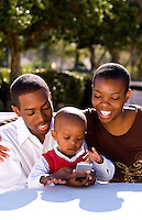 Attractive black African American family with young boy playing with I phone cell phone at home in sunshine outdoors smiling and happy