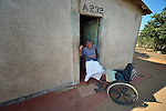 Caroline Mandishona climbs into her wheelchair in the doorway of her home in Bulawayo, Zimbabwe. Mandishona suffered cerebral palsy and uses a wheelchair provided by the Jairos Jiri Association with support from CBM-US.