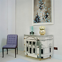 A master bedroom with a painting of the Infant of Prague by Grillo Demo hanging above a Fornasetti cabinet. The 1940s chair is by Marc du Plantier.