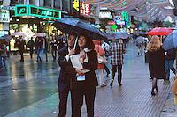 Couple strolling on pedestrian shopping street Calle de Preciadas between Puerta del Sol and Plaza de Callao in light rain. Madrid, Spain.