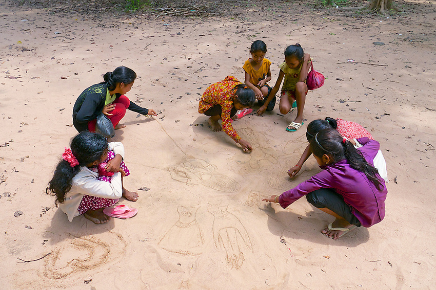 Local children (Girls) drawing in the sand near the Pre-Angkorian temple complex of Sambor Prei Kuk (Khmer:  is located about 30 kilometers to the north of the town of Kampong Thom, Cambodia. It was also known as Isanapura, and was the capital of the Chenla Kingdom.<br /> <br /> Located on the Eastern bank of Tonle Sap close to the Sen River, the central part of Sambor Prei Kuk is divided into three main groups. Each group is located in a square lay out surrounded by a brick wall. The structures of the overall archaeological area were constructed at variable times: the southern and north groups (7th century) by Isanavarman I, and the central group (later date). <br /> <br /> The buildings of Sambor Prei Kuk are characteristic of the Pre-Angkorean period with a simple external plan. The principal material is brick, but sandstone is also used for certain structures. Architectural features include numerous prasats, octagonal towers, shiva lingams and yonis, ponds and reservoirs, and lion sculptures. Sambor Prei Kuk is located amidst mature sub-tropical forests with limited undergrowth. The area has been mined and could still contain unexploded ordnance.