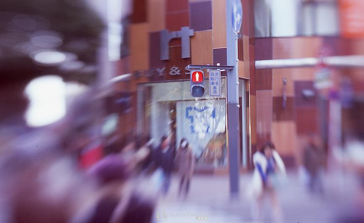A pedestrian stop light in front of a large store in trendy Sakae, Nagoya. Photo taken using a selective focus lens on positive slide film.