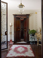 Wrought iron and glass doors open into a curved entrance hall painted with trompe l'oeil panelling