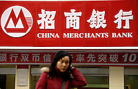 A girl walks pass a branch of China Merchants Bank (CMB) in Nanchang, Jiangxi province, China..
