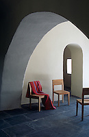 A group of contemporary wooden chairs in the slate-tiled entrance hall