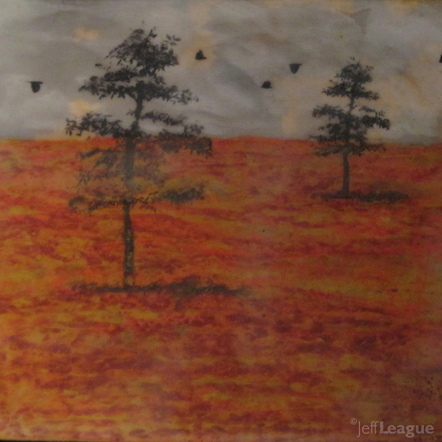 Mixed media encaustic painting with photo transfer of autumn trees on indian red ground with crows in blue gray sky.