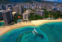 Aerial view of Hilton Hawaiian village on Waikiki beach with blue ocean and other hotels.