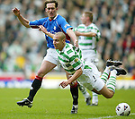 Henrik Larsson in typical feet up pose as he is challenged by Fernando Ricksen, Celtic v Rangers 10th March 2002