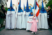 Procession for 'Semana Santa', Holy Week in Seville, Spain (Sevilla) - a young girl with open arms reaches out to hug a hooded girl in the parade.