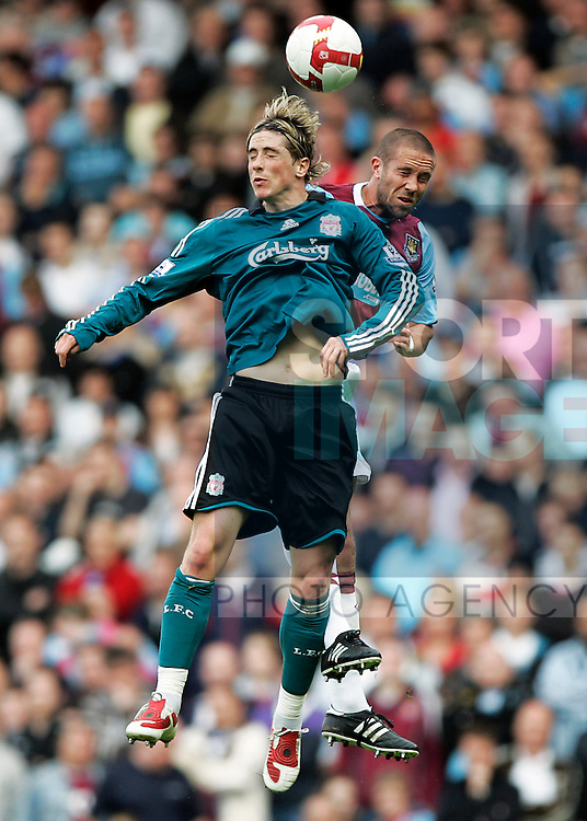 Fernando Torres of Liverpool and Matthew Upson of West Ham United jump for the ball
