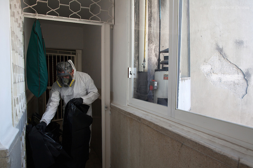 """Donovan puts on his Hazmat suit before beginning a forensic cleaning in Mexico City, Mexico on January 14, 2016. The decomposed body of a man in his 50s was found on the floor of his mother's bedroom, days after he had died of an intestinal obstruction. Because of her physical disability, the mother of the deceased – who had been her caregiver – was unable to move enough to make an emergency call. As a consequence, she was trapped in the room for three days with the body of her son – and without food or water - before help arrived. Donovan Tavera, 43, is the director of """"Limpieza Forense México"""", the country's first and so far the only government-accredited forensic cleaning company. Since 2000, Tavera, a self-taught forensic technician, and his family have offered services to clean up homicides, unattended death, suicides, the homes of compulsive hoarders and houses destroyed by fire or flooding. Despite rising violence that has left 70,000 people dead and 23,000 disappeared since 2006, Mexico has only one certified forensic cleaner. As a consequence, the biological hazards associated with crime scenes are going unchecked all around the country. Photo by Bénédicte Desrus"""
