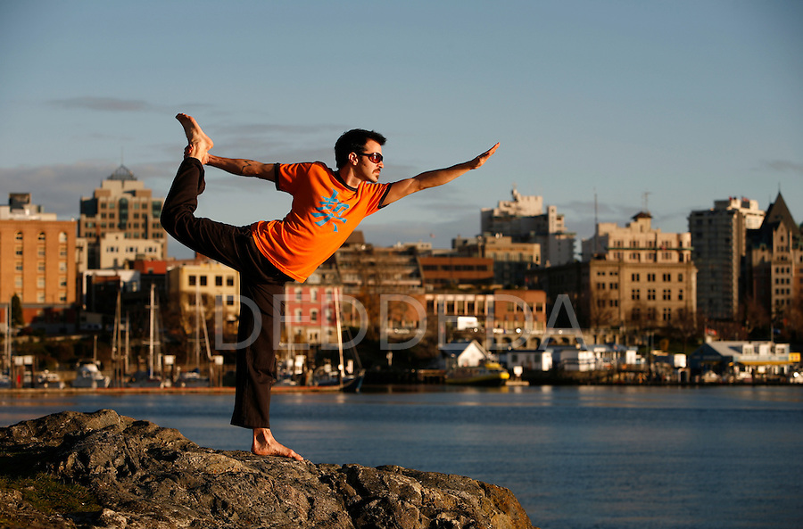 A young man holds a yoga pose in Victoria, BC's Inner Harbour, Canada.