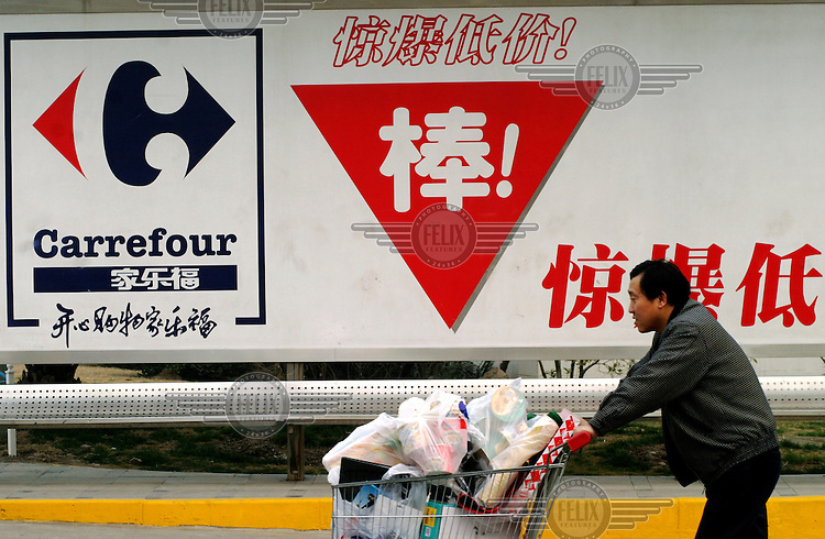 A man pushes a cart full of just purchased goods past a Carrefour sign. The retail giant plans to continue its expansion by opening up new hypermarket stores at an average rate of one per month.