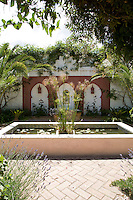 A raised pond, complete with gold fish, forms the central feature of the brick paved courtyard