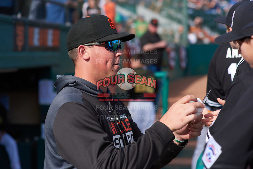 San Jose Giants pitcher John Gavin (19) signs an autograph before a California League game against the Visalia Rawhide on April 13, 2019 at San Jose Municipal Stadium in San Jose, California. Visalia defeated San Jose 4-2. (Zachary Lucy/Four Seam Images)