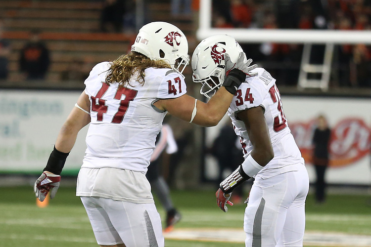 Peyton Pelluer (47) and Jalen Thompson (34), members of the Washington State defense, celebrate a big play during the Cougars Pac-12 Conference road comeback victory over the Oregon State Beavers, 35-31, on October 29, 2016, at Reser Stadium in Corvallis, Oregon.