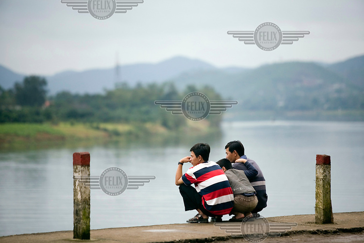 Men sitting on the banks of the Song Houng (The Perfume) River.