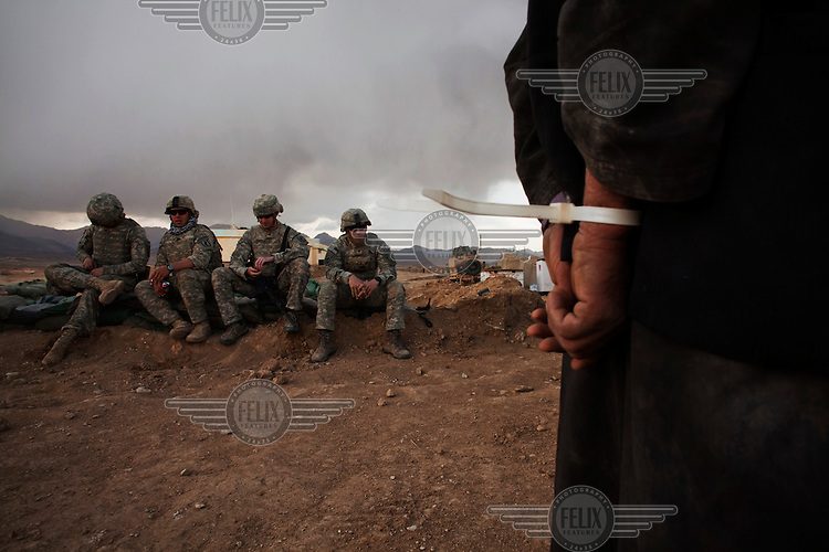 A Taliban detainee, Latullah, stands handcuffed and blindfolded as US Army soldiers look on at Jaghatu Combat Outpost. He was picked up with Zadiullah, a high-value Taliban target and spokesperson, in a joint US Special Forces and Afghan National Police (ANP) operation and then interrogated. He was found with Taliban propaganda, mortars and ammunition in his home.