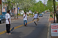 Boys ride skateboards in street as a car approaches.