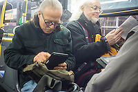 A reader with his electronic book ereader on a bus in New York on Saturday, February 2, 2013. (© Richard B. Levine)