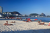 BRAZIL, Rio de Janiero, bright red umbrellas line the sand at Copacabana Beach