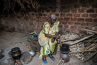 Uganda, Kasawo. Joweria Nalwadda runs a coffee plantation and a small shop. Her at home she's cooking with her Biolite stove that can charge a light and her phone.