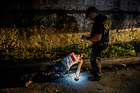 "Quezon City, PHILIPPINES - OCTOBER 08: Scene of the Crime Police Investigators conduct their investigation as alleged drug dealer, the police named as Jesse Judas, lays in the street, shot dead after a ""buy and bust"" operation on October 8, 2016 in the San Francisco del Monte neighbourhood of Quezon City, Philippines. Neighbours heard 3-5 number gunshots after 4am. Judas was ranked as number out of the top 10 drug dealers  in the Masambong area and Del Monte area. The ""buy and bust"" operation started at 4am and they bought 200 pesos worth of Shabu, the local name for Methamphetamine.  <br /> Photo by Daniel Berehulak for The New York Times"