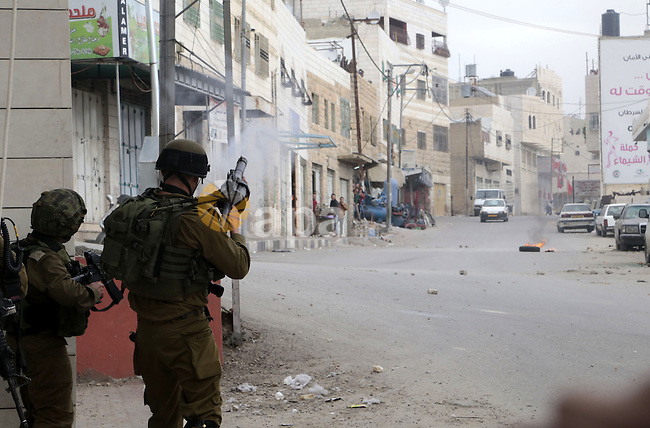 A member of Israeli security forces fires tear gas towards Palestinian protesters during clashes following a rally marking the 27th anniversary of the founding of the Islamist group of Hamas, in the West Bank city of Hebron, December 12, 2014. Photo by Muhesen Amren