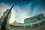 Garden City, New York, USA. December 12, 2015. Metal Rocket sculpture appears to soar into sky in front of the Cradle of Aviation Museum, with Nassau County Firefighters Museum at left.